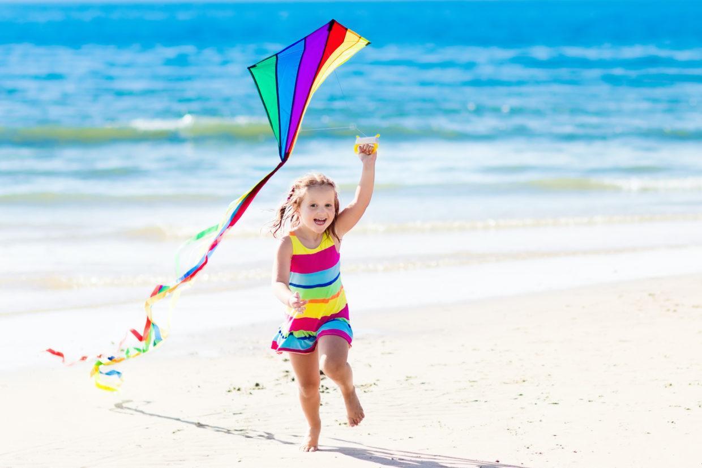 meisje met vlieger op strand