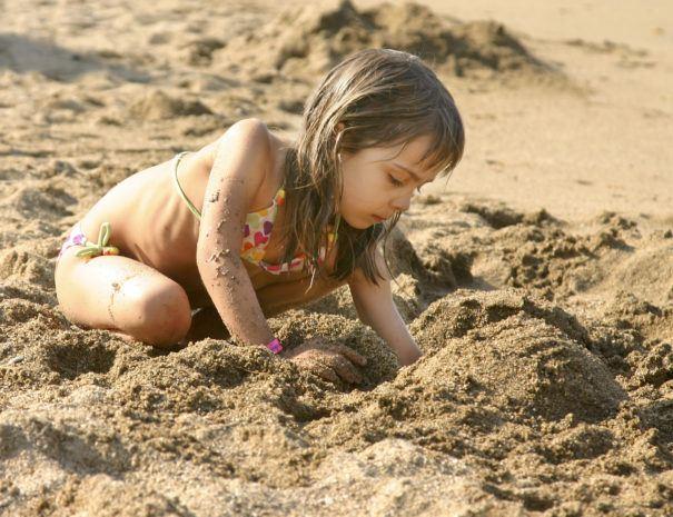 kindje graaft op het strand